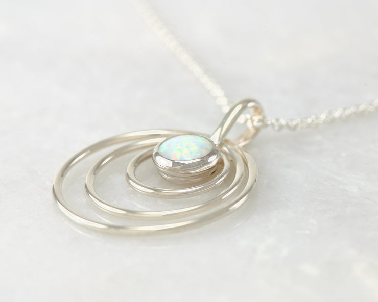 Silver opal circles necklace on white marble