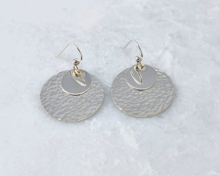 Silver polished hammered discs earrings on white marble