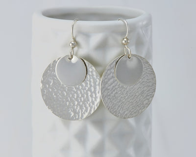 Silver hammered discs earrings on geometric vase
