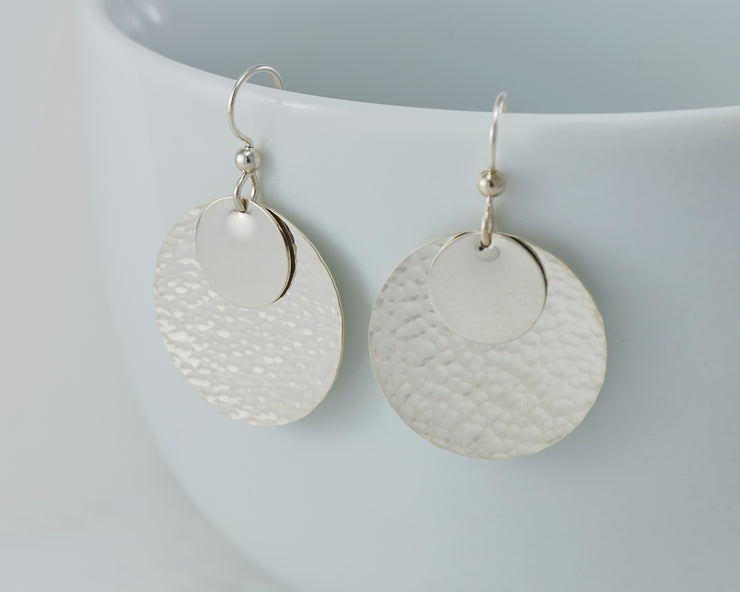 Silver hammered discs earrings on white cup