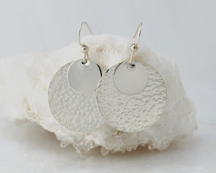 Silver hammered discs earrings on white rock