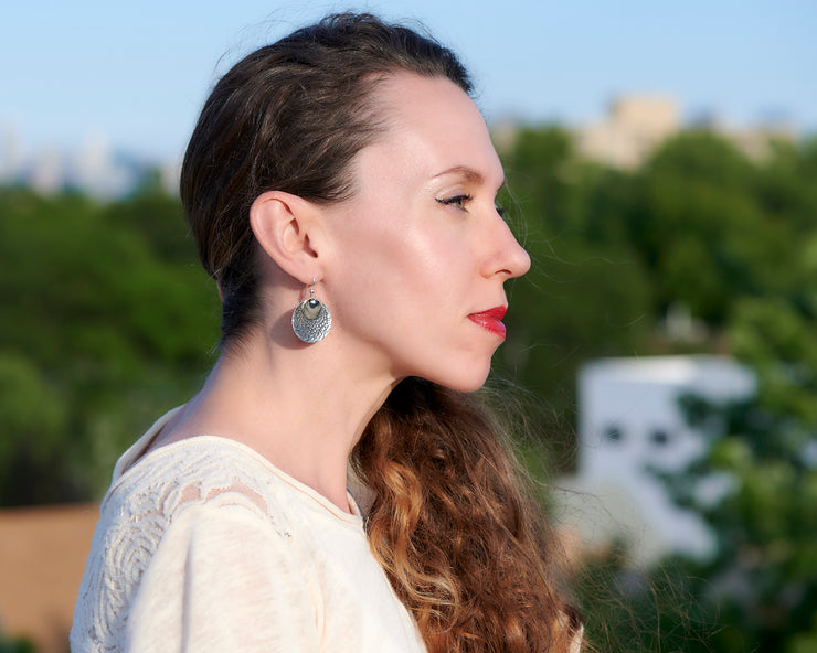 Woman wearing silver hammered discs earrings