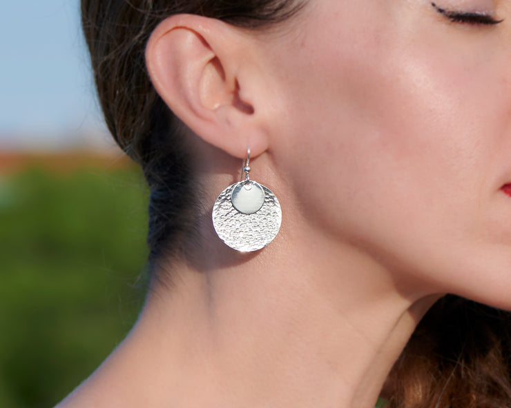 close up of woman wearing silver hammered discs earrings