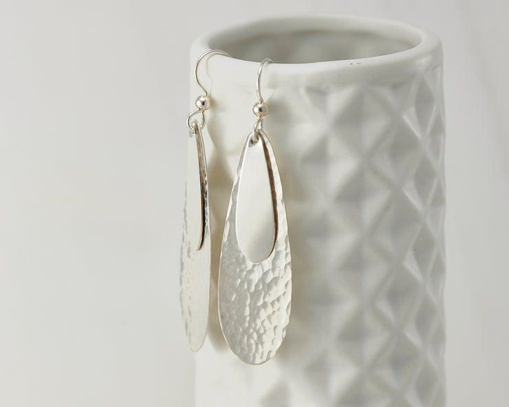 Silver teardrops earrings on geometric vase