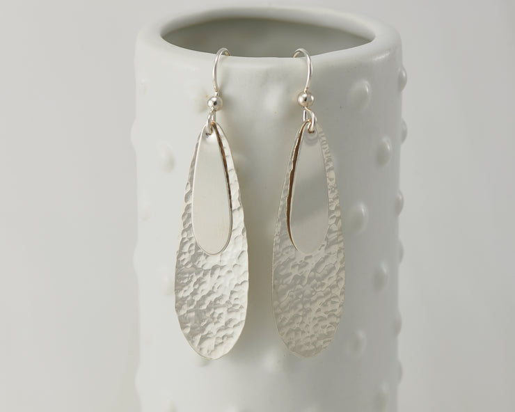 Silver polished teardrops earrings on dotted vase