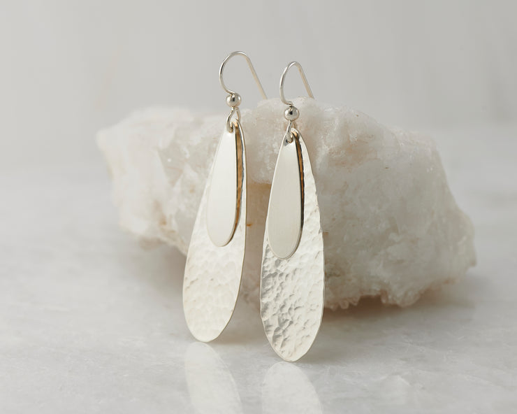 Silver teardrops earrings on white rock
