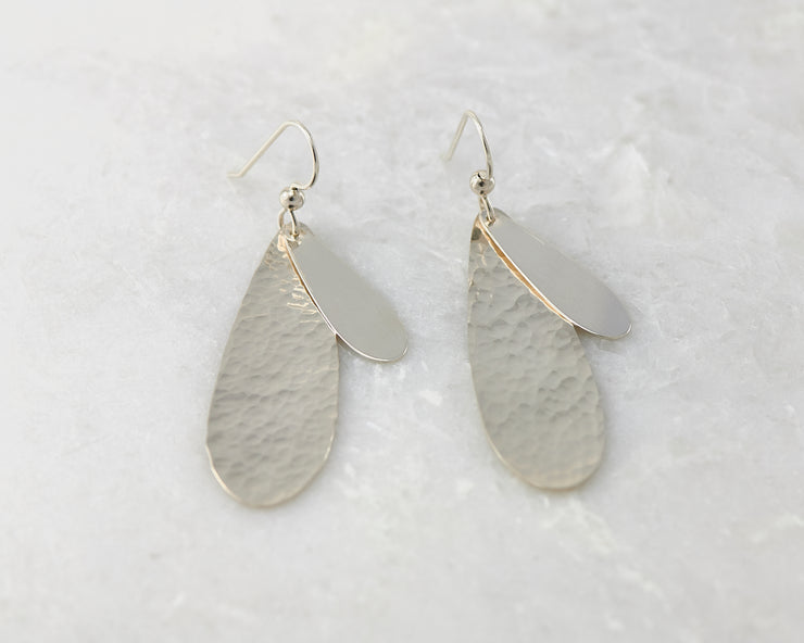 Silver polished teardrops earrings on white marble