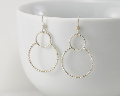 Silver beaded circles hoop earrings on white cup