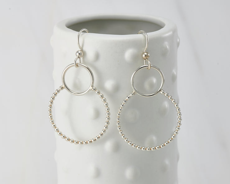 Silver polished beaded circles hoop earrings on dotted vase