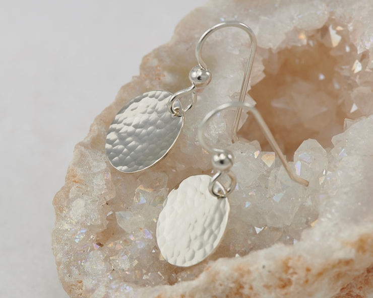 Small silver earrings on a piece of gypsum