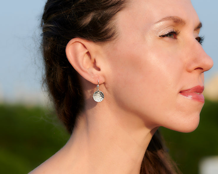Silver earrings being worn by a woman