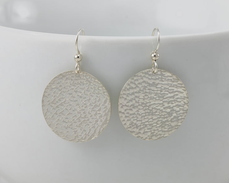 Silver disc earrings hanging from a white cup