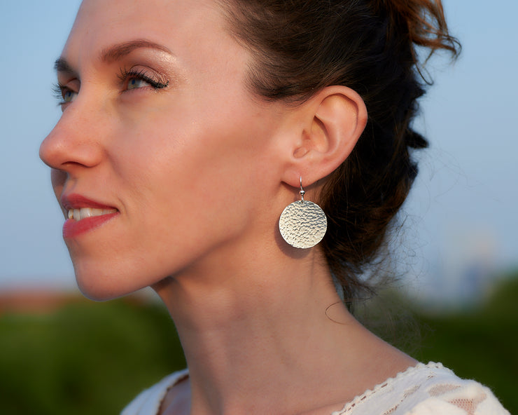 Silver dangle earrings being worn by a woman