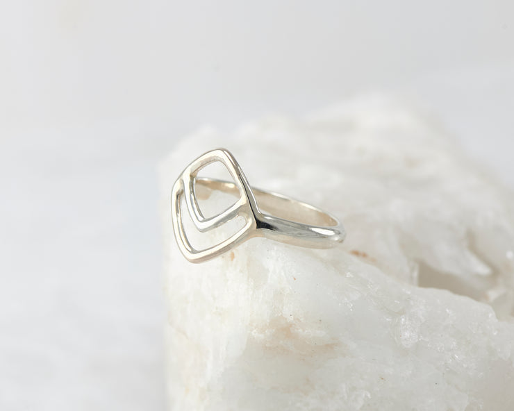 Silver geometric ring on white rock