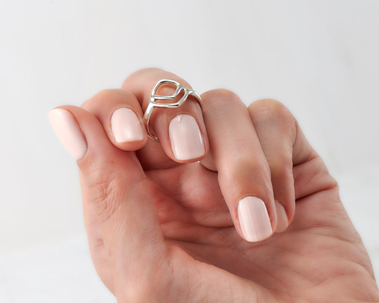 Woman holding geometric silver ring