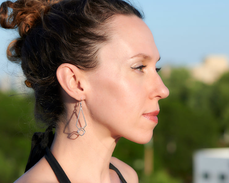Woman wearing silver beaded geometric earrings