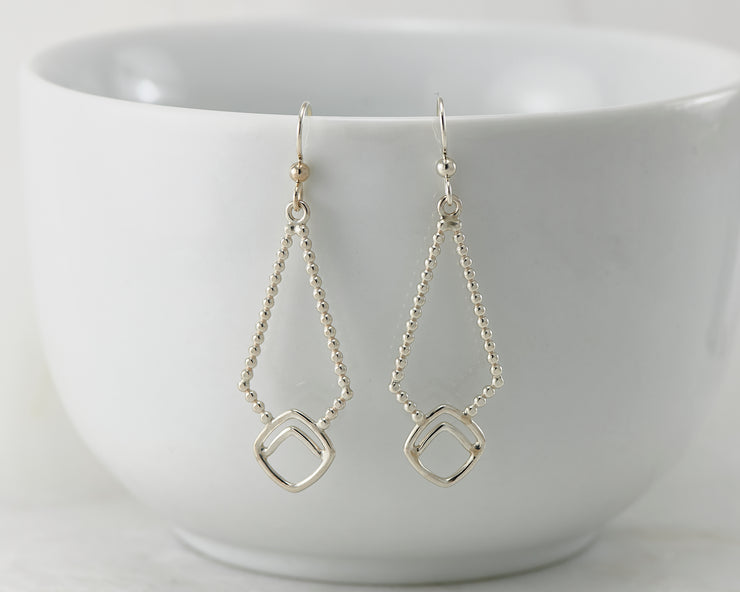 Silver beaded geometric earrings on white cup