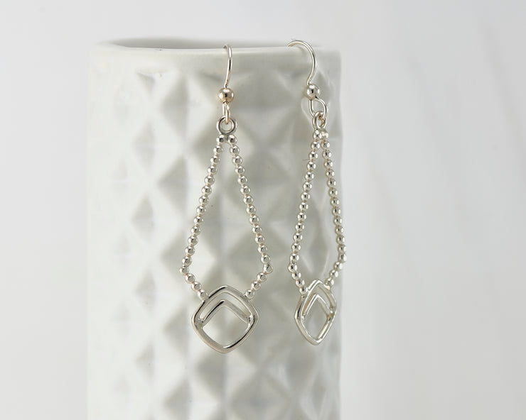 Silver beaded geometric earrings on geometric vase