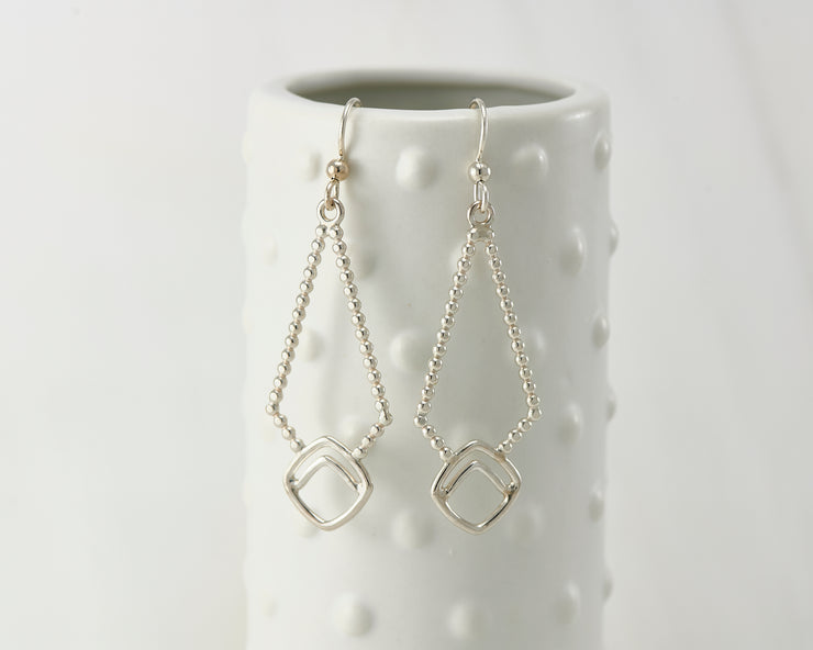 Silver polished beaded geometric earrings on dotted vase