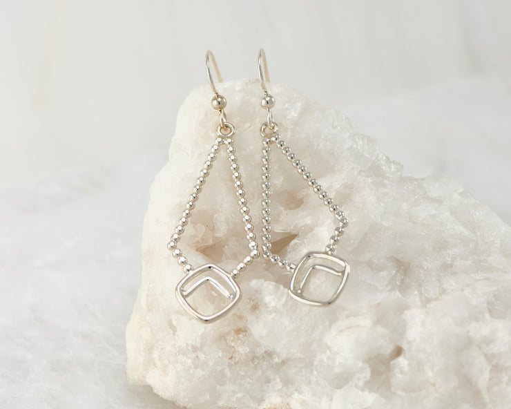 Silver beaded geometric earrings on white rock