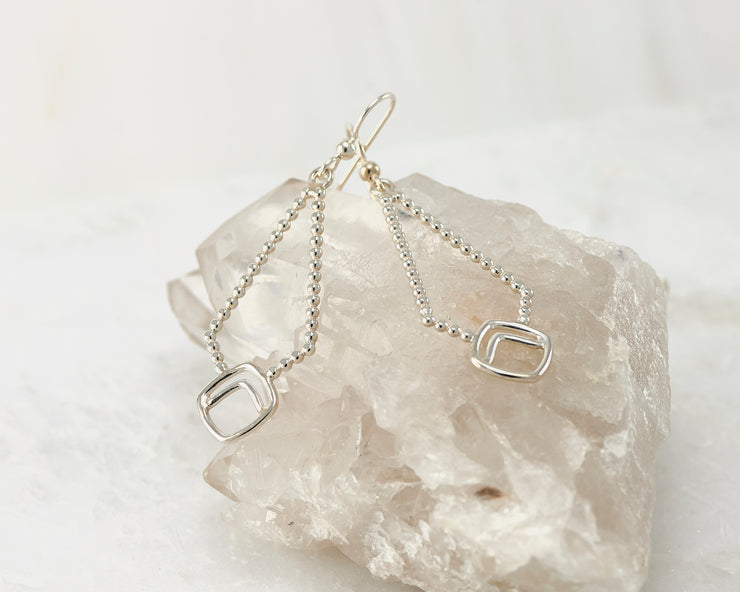Silver beaded geometric earrings on crystal rock
