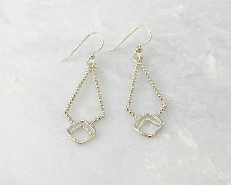 Silver polished beaded geometric earrings on white marble