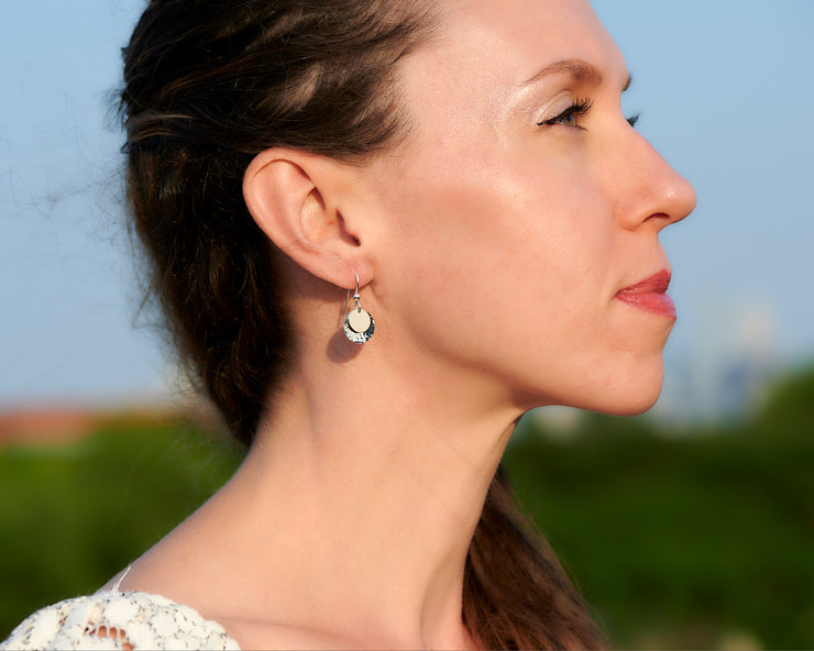 woman wearing silver and gold disc earrings