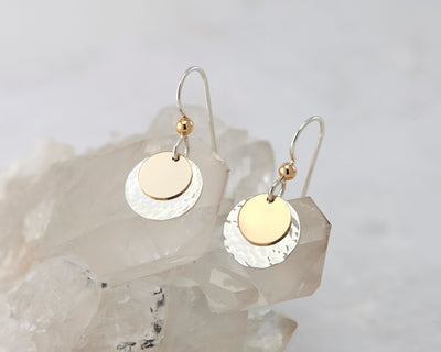 silver and gold disc earrings on quartz