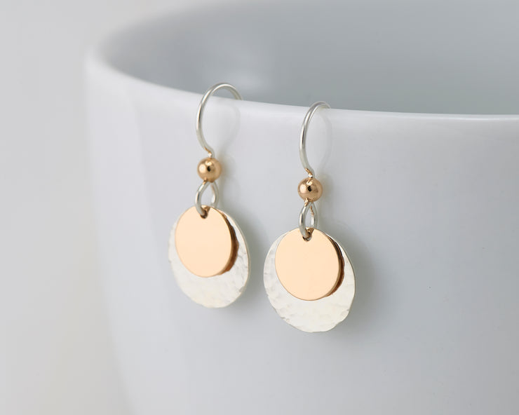 silver and gold disc earrings on white cup