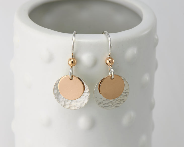 silver and gold disc earrings on dotted vase