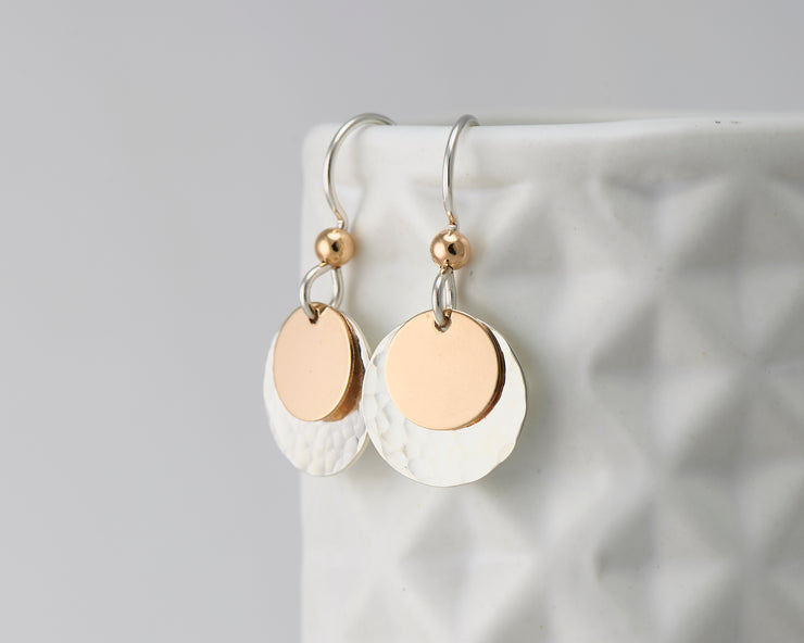 silver and gold disc earrings on geometric vase