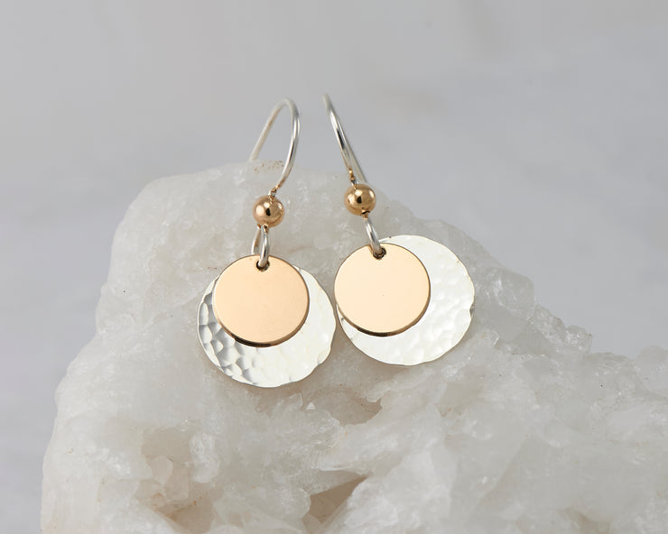 Silver dangle and gold disc earrings on white rock