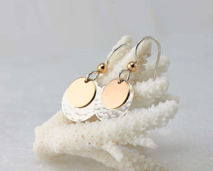 silver and gold disc earrings on coral