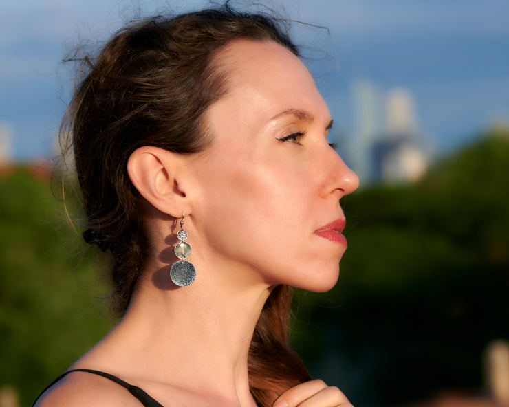 Silver disc earrings being worn by a woman
