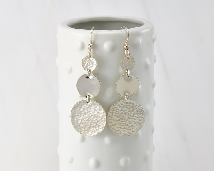 Circle Hammered earrings hanging on a dotted vase