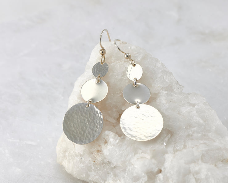Hammered Dangle Earrings shown on a white rock