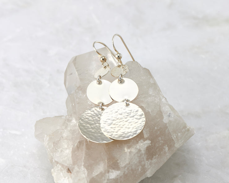 Hammered Dangle Earrings shown on a crystal rock
