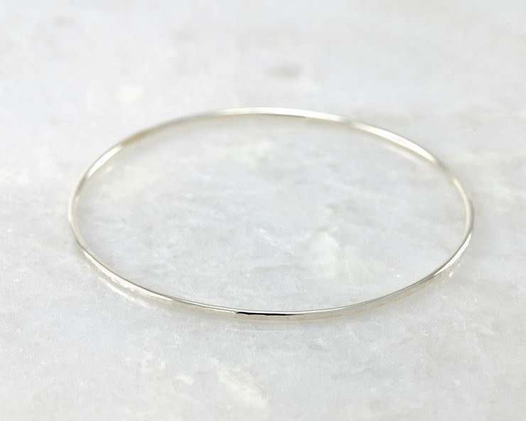 latch style hammered silver bangle bracelet open on marble