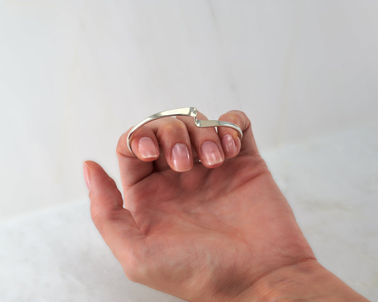 woman holding silver wave bangle bracelet