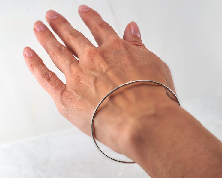 Woman wearing silver hammered bangle bracelet