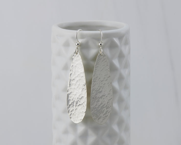 silver hammered teardrop earrings on geometric vase