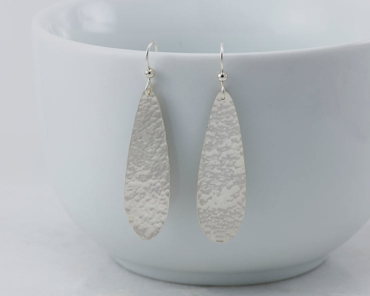 silver hammered teardrop earrings on white cup