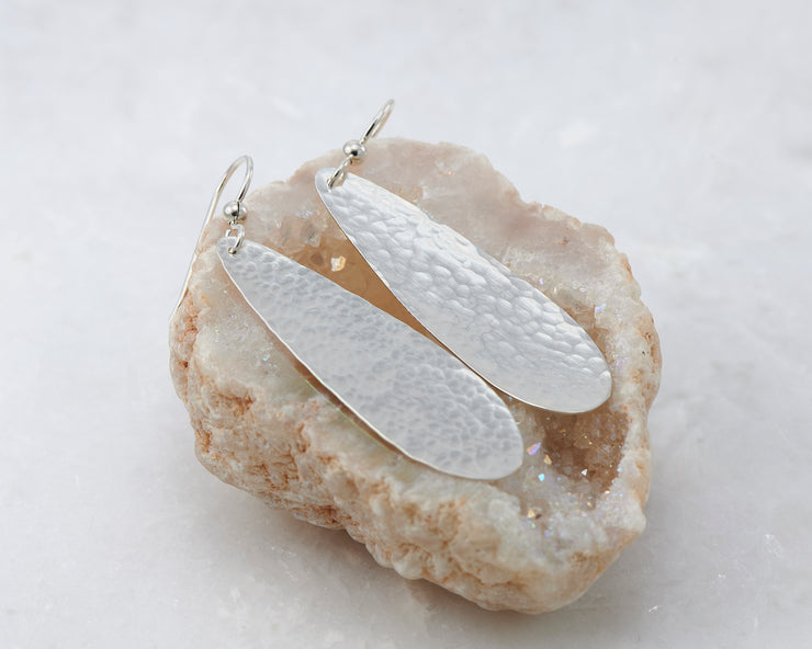 silver hammered teardrop earrings on quartz