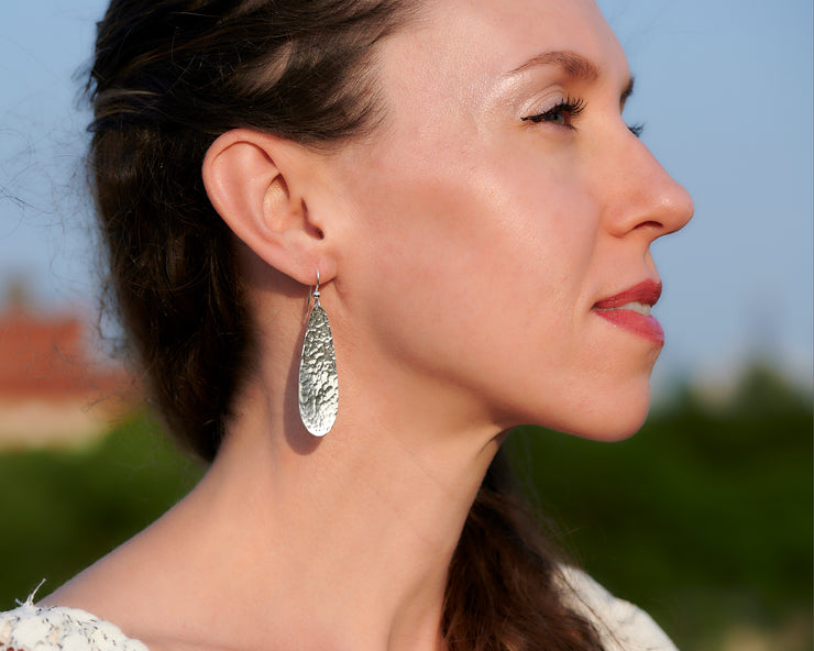 woman wearing silver hammered teardrop earrings
