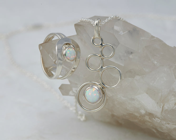 Silver opal ring and silver opal necklace on crystal
