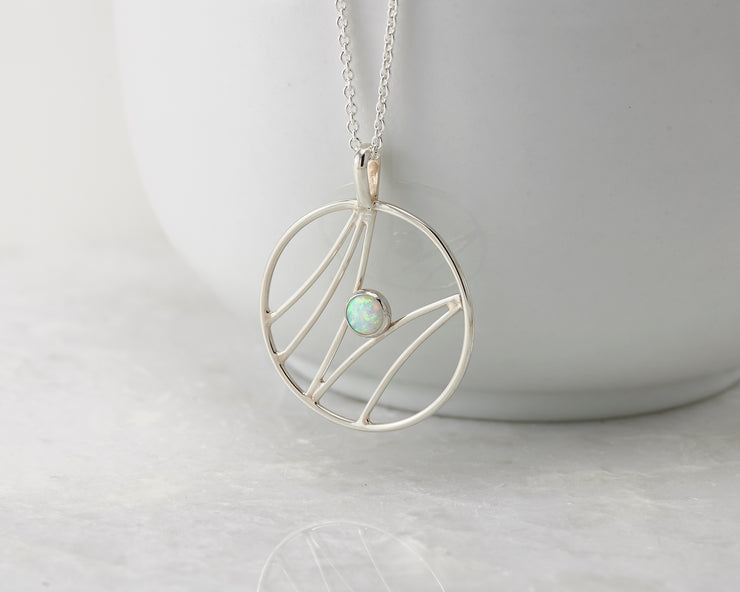 silver opal pendant necklace hanging from white cup