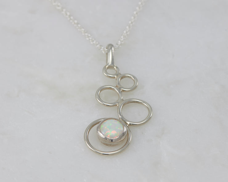 silver opal pendant on white marble