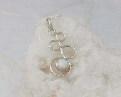 Silver opal pendant on white rock