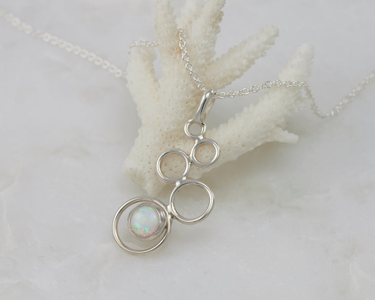 opal gemstone silver necklace on coral