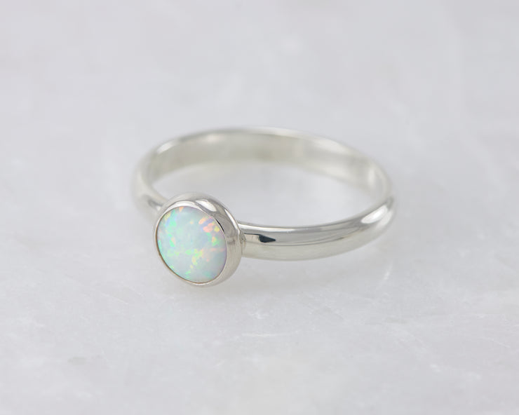 simple opal silver ring on white marble